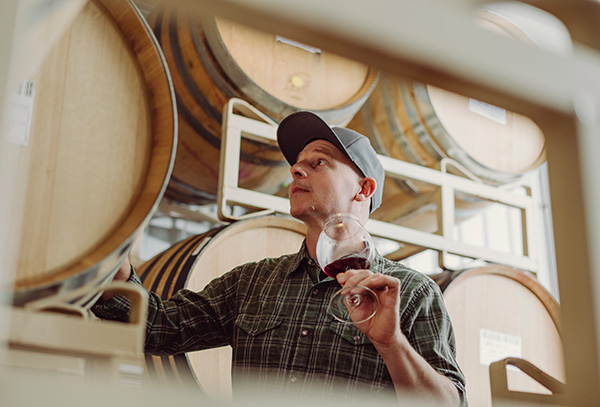 Ryan looking at barrels while holding a glass of wine